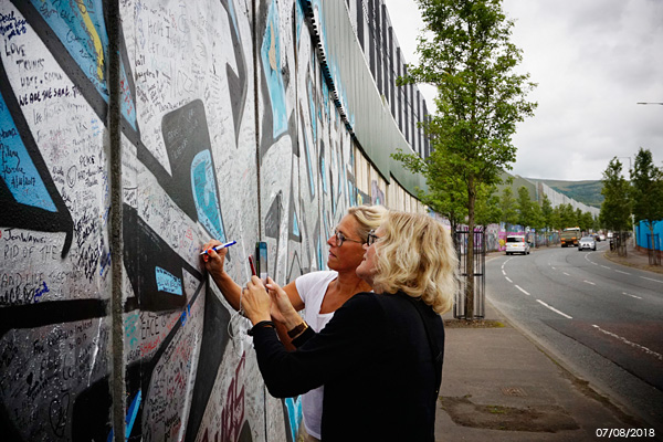 Christina Ica Hörbäck with her sister, Annis Andersson Josefson, at the Peace Wall which separates the nationalist Falls Road and unionist Shankill Road areas of West Belfast.
